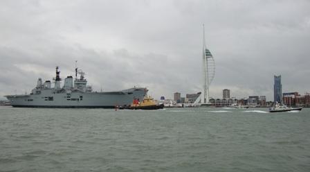 The HMS Ark Royal vertrekt met sleepboten die haar de haven uithelpen