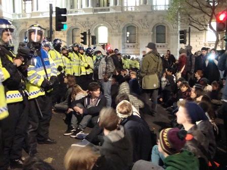 De politie probeert de omstaande studenten terug te duwen, deze groep weigert te vertrekken