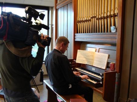 Father Elliot Mark Smith wordt door cameraman Jamie gefilmd aan het orgel