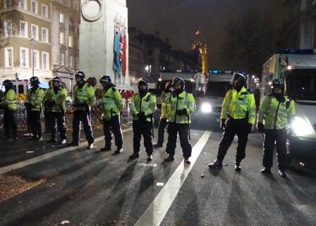De tweede rij politie die omstanders weg houdt van de vastgehouden groep studenten in het midden van Whitehall